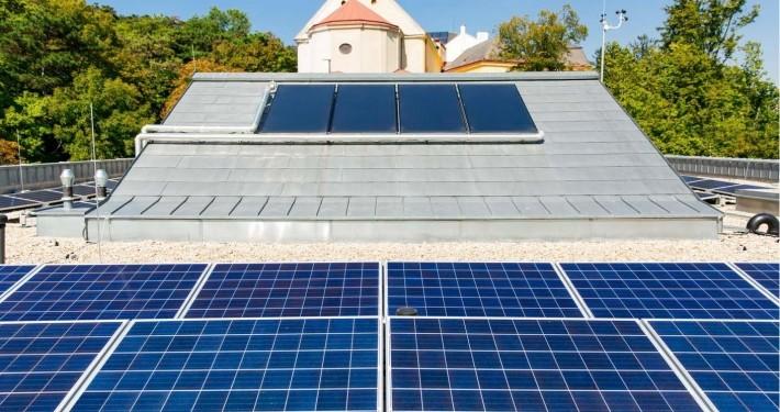 Im Hintergrund des Bildes erkennt man Solarthermie Flachkollektoren, im Vordergrund polykristalline Solarmodule